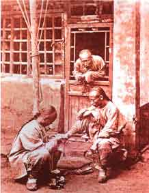 Médico chino atendiendo a un paciente en la calle (1874). [Hulton Getty]